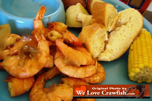 Photo of fresh, boiled Louisiana Shrimp along with French Bread, corn on the cob and boiled potatoes